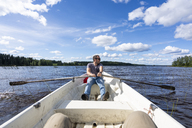 Finland, Man rowing in a boat on a lake - KKAF01729