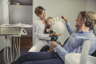 Little boy siting on dentist's lap, playing with a balloon, father smiling - MFF04522