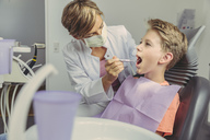 Dentist examining boy's teeth with dental instruments - MFF04528