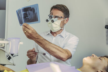Dentist looking at x-ray image before treatment - MFF04555