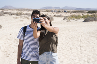 Young couple having fun on the beach, taking smartphone selfies - PACF00108