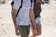 Young couple walking on the beach, holding hands - PACF00111