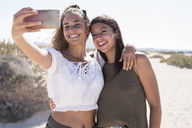 Girlfriends having fun on the beach, taking smartphone selfies - PACF00114