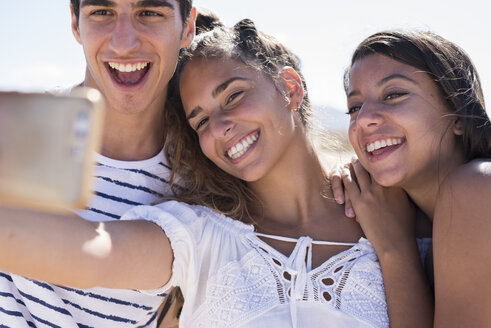 Friends having fun on the beach, taking smartphone selfies - PACF00117