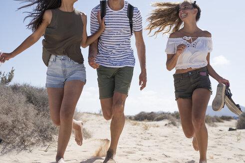 Friends having fun, running barefoot on the beach - PACF00120