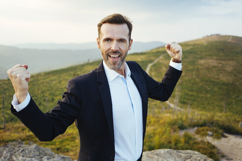 Portrait of self-confident businessman standing on top of a mountain - BSZF00583