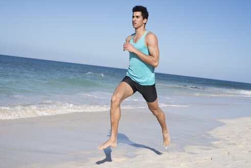 Spain, Canary Islands, Fuerteventura, young man running on the beach - PACF00134