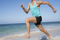 Spain, Canary Islands, Fuerteventura, young man exercising on the beach - PACF00137