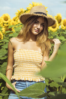 Young woman with a straw hat in a field of sunflowers - ACPF00324