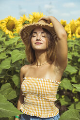 Young woman holding a straw hat on her head in a field of sunflowers - ACPF00327