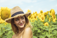 Young woman with a straw hat smiling in a field of sunflowers - ACPF00330
