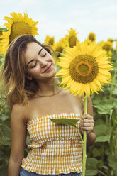 Young woman smiling holding a sunflower - ACPF00333