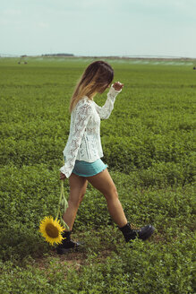 Young woman walking holding a sunflower in a green field - ACPF00336