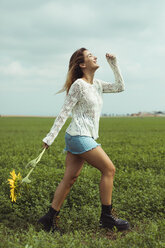 Young woman walking, holding a sunflower in a green field - ACPF00339