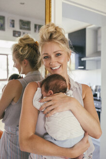 Portrait of happy mother holding her baby close in front of mirror at home - MFF04610