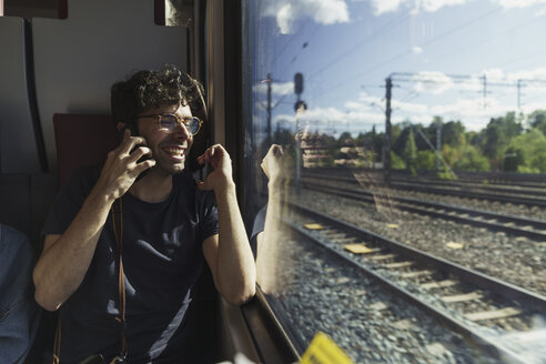 Happy man traveling by train talking on cell phone - KKAF01776