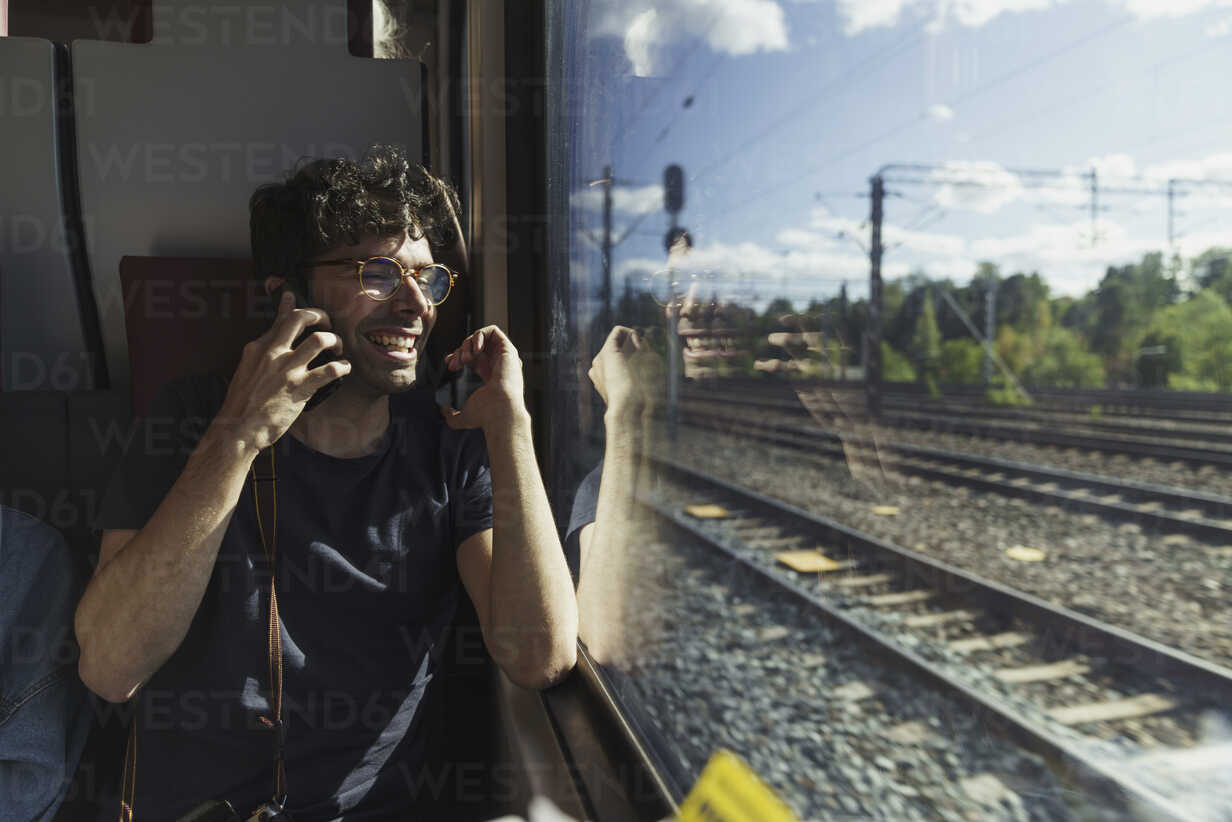 Happy man traveling by train talking on cell phone - KKAF01776 - Kike Arnaiz/Westend61