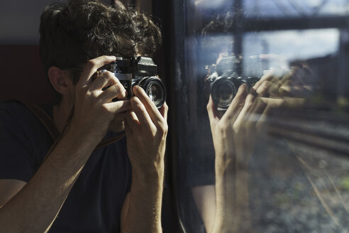 Man traveling by train taking picture with old-fashioned camera - KKAF01779