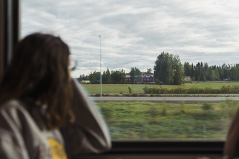 Woman traveling by train looking out of window - KKAF01785