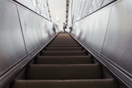 Woman standing on escalator of underground station - KKAF01788