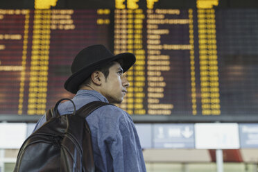 Young man with hat and backpack at arrival departure board at the airport - KKAF01791
