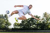 Young man kicking soccer ball - STSF01741