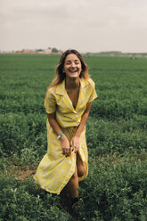 Young woman walking in a green field - ACPF00341