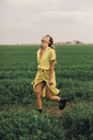 Young woman walking in a green field - ACPF00344
