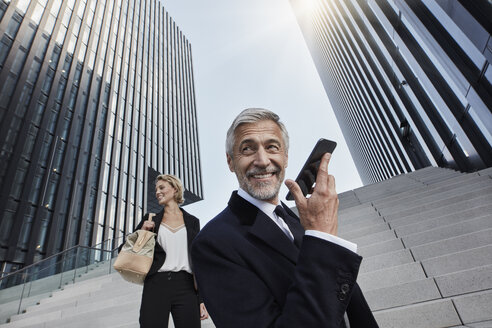 Portrait of content businessman on the phone with his business partner in the background - RORF01468