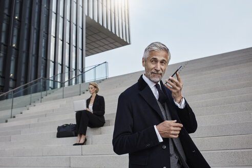 Portrait of businessman on the phone while business woman working on laptop in the background - RORF01474