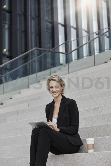 Portrait of smiling businesswoman with tablet and coffee to go sitting on stairs in front of modern office building - RORF01480