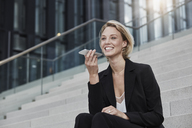 Portrait of smiling businesswoman  sitting on stairs outdoors talking on mobile phone - RORF01483