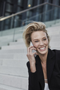 Portrait of laughing businesswoman on the phone sitting on stairs outdoors - RORF01486