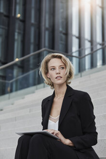 Portrait of blond businesswoman with tablet sitting on stairs outdoors - RORF01489