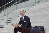Portrait of fashionable businessman with travelling bag and tablet sitting on stairs - RORF01495
