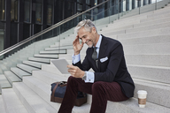 Fashionable businessman with travelling bag and coffee to go sitting on stairs using tablet - RORF01498