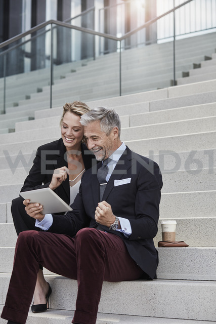 Two business people sitting together on stairs looking at tablet - RORF01504