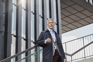Portrait of mature businessman standing on stairs in front of modern office building looking at distance - RORF01507