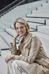 Portrait of smiling blond businesswoman wearing beige trenchcoat sitting on stairs - RORF01522