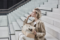 Fashionable blond businesswoman wearing beige trenchcoat sitting on stairs with travelling bag - RORF01525