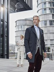 Germany, Duesseldorf, portrait of fashionable mature businessman in front of modern business building - RORF01531