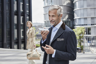 Germany, Duesseldorf, portrait of  mature businessman talking on mobile phone - RORF01534