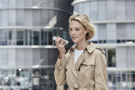 Germany, Duesseldorf, portrait of  blond businesswoman wearing beige trenchcoat using smartphone - RORF01537