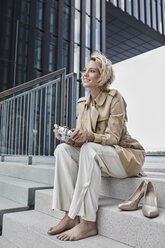 Portrait of young fashionable woman with digital camera sitting barefoot on stairs - RORF01543