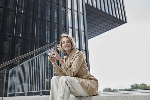 Portrait of young blond woman with digital camera sitting on stairs - RORF01546
