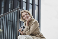 Portrait of smiling blond woman with digital camera sitting on stairs - RORF01549