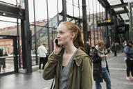 Young woman talking on mobile phone with friend in background at city - MASF08616