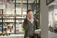 Young woman looking at box while talking through mobile phone at store - MASF08619