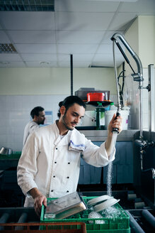 Chef spraying water on plates in commercial kitchen - MASF08649