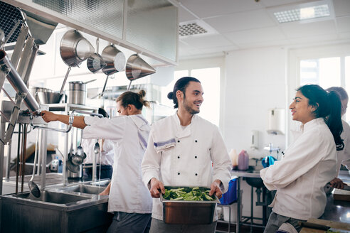 Male and female chefs communicating while preparing food in commercial kitchen - MASF08658